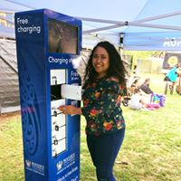 An event-goer uses the Massey University-branded phone charging station