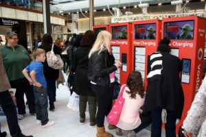A crowd gathers round a phone charging station at Westfield