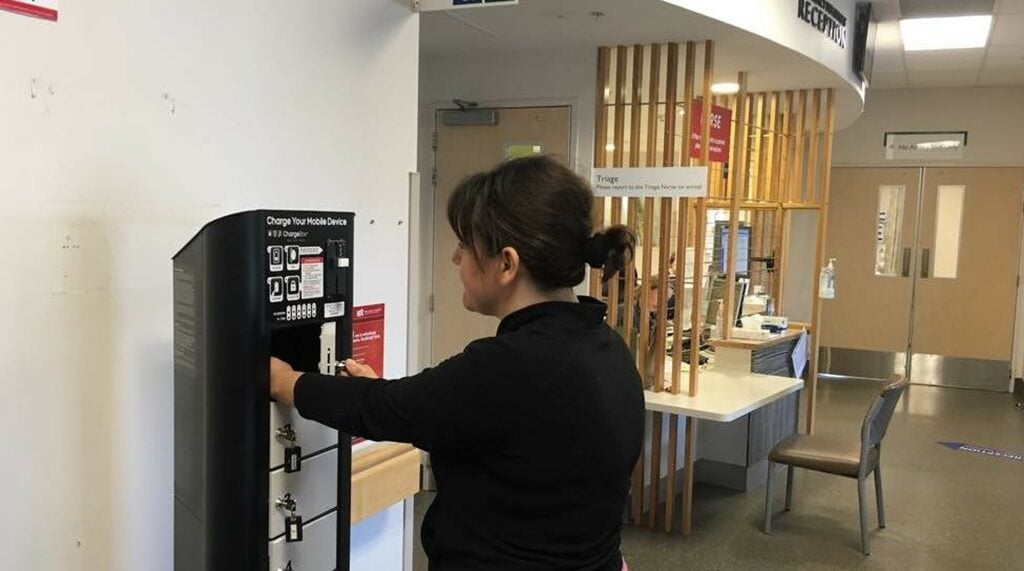 A Hutt Hospital visitor uses the hospital's phone charging station, provided by ChargedAs.